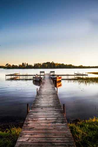 Boat_dock_lake_side_resort_john_boats_fishing_boats_lake_front_sunset_vertical_color_water_s_edge_vacation_summer_time_fishing_season_calm_water_glassy_oealol
