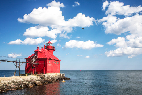 Red_lighthouse_sea_side_great_lakes_cumulous_clouds_point_calm_water.summer_skies_calm_seas_coast_guard_station_a2zbsi