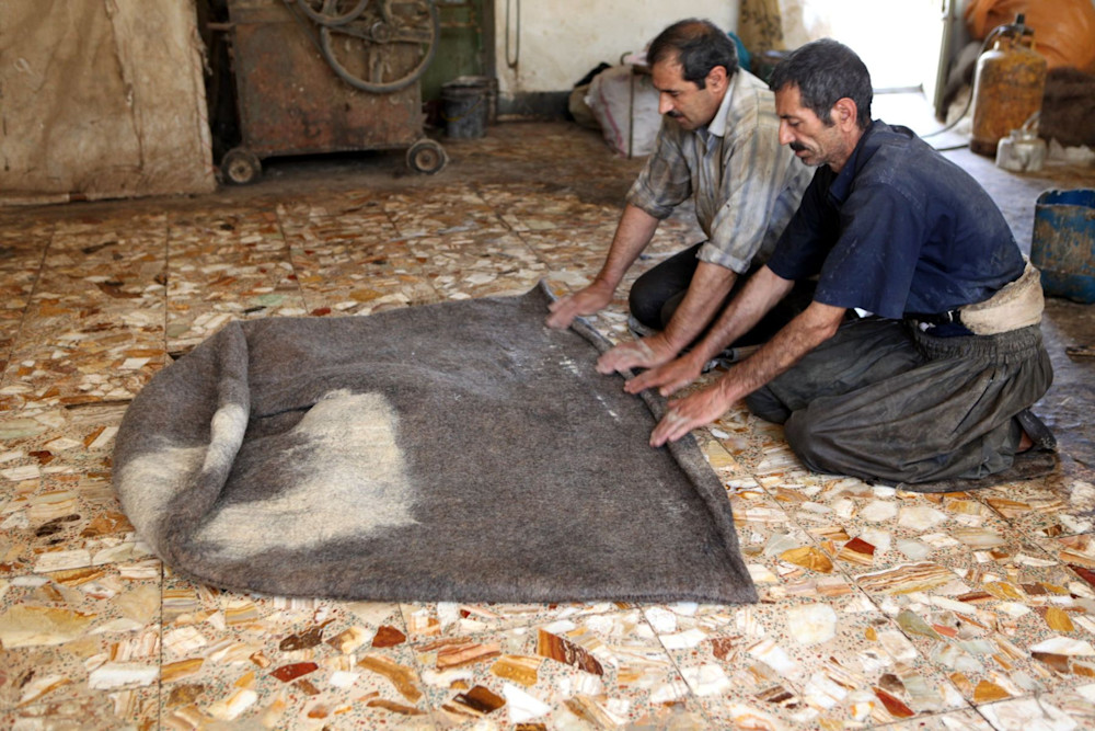 Men making felted fabric