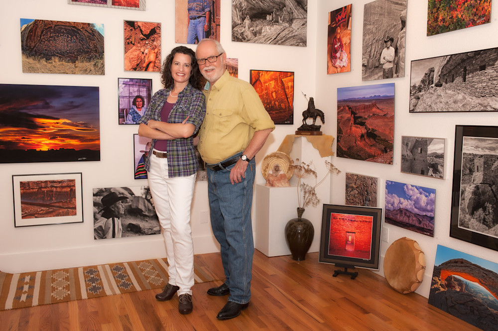Christina and Richard Stefani smiling in front of their artwork at Stefani Fine Art.