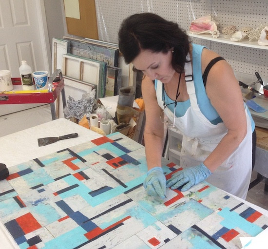 Artist Shirley Williams working in the art studio on a large encaustic wax painting
