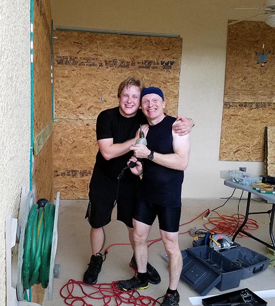Kevin and Nicholas Grass helping their neighbor build hurricane shutters for Hurricane Irma.