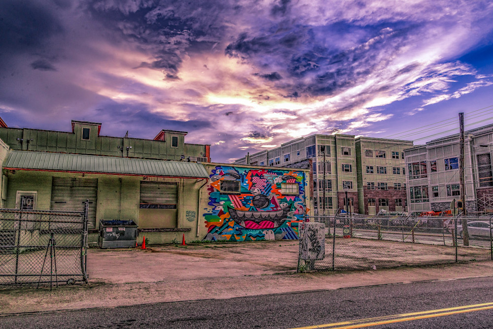 A colorful and cloudy sky in the background with a small parking lot in the foreground