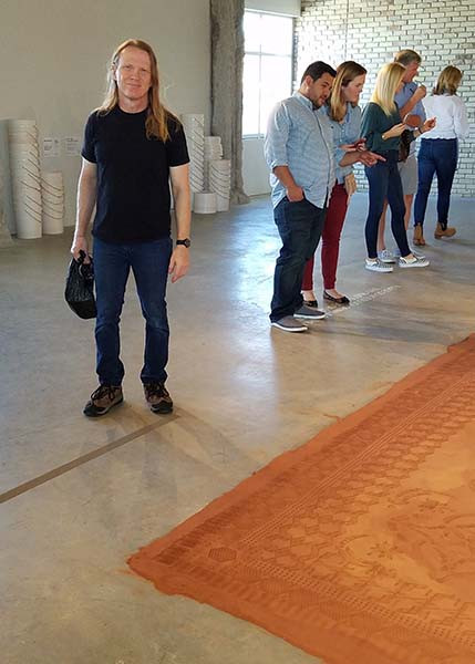 Florida artist Kevin Grass next to the loose red dirt rug that won the time-based art competition at Art Prize 2017.