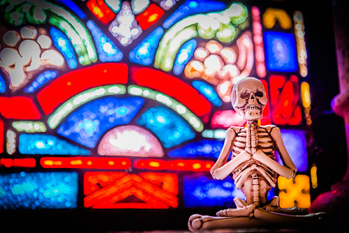 A yogi skeleton in front of one of the stained-glass windows in the mausoleum chapel