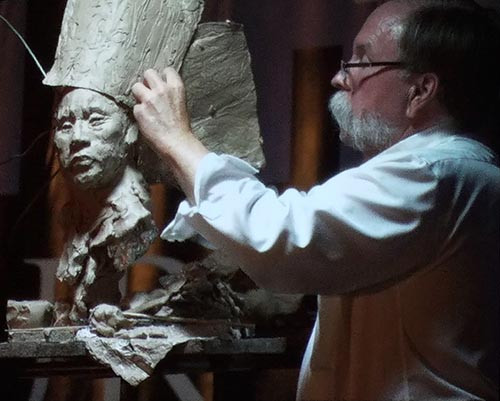 John Coleman transforming a sculpture of a girl into a Sioux warrior at the FACE convention in Miami.