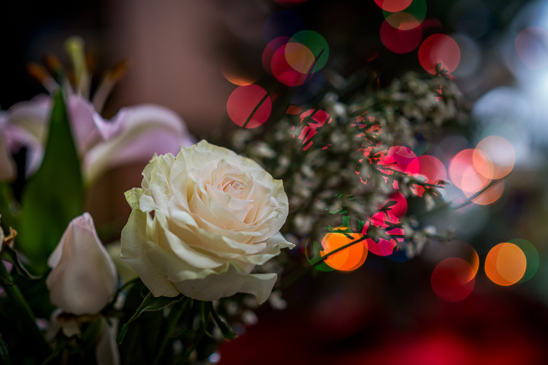 A bouquet of flowers with the bokeh of Christmas lights in the background