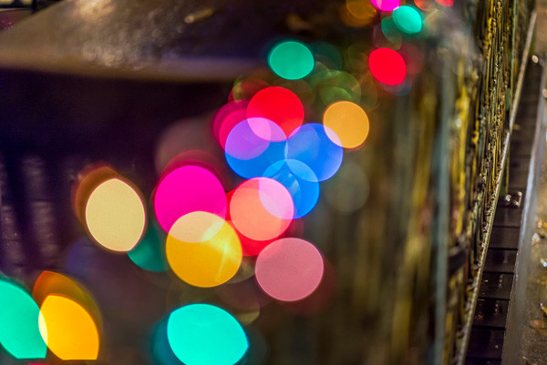 A string of holiday lights along the railing of a patio cafe