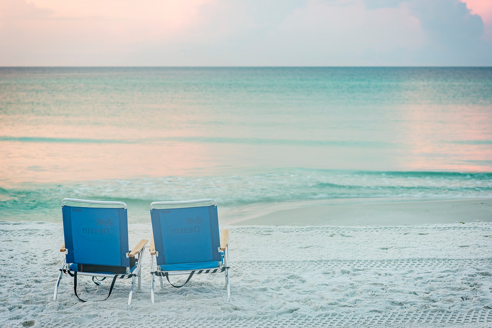 A colorful sunrise beach scene of two empty chairs in Destin, Florida