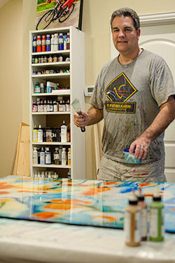 Sports artist Mark Trubisky painting in his studio.