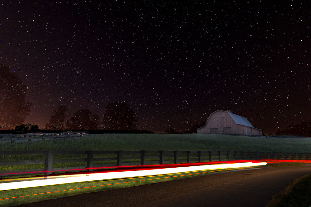 A barn in a field on a starry night