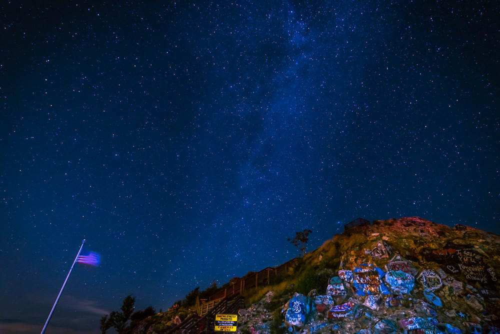 The Milky Way with a backdrop of rocks and an American flag