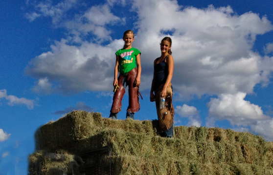 Girls on hale bale stack