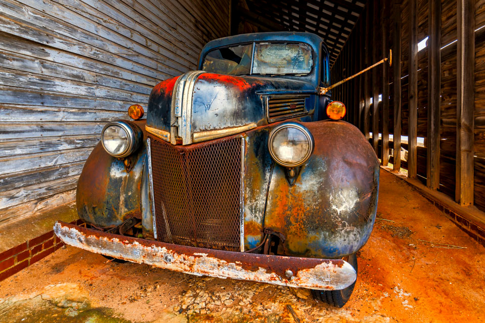 An old 1940s Ford pickup truck was tucked inside an old barn in rural Georgia. The classic pickup truck is covered in rust, but much of the original blue paint still shows through.