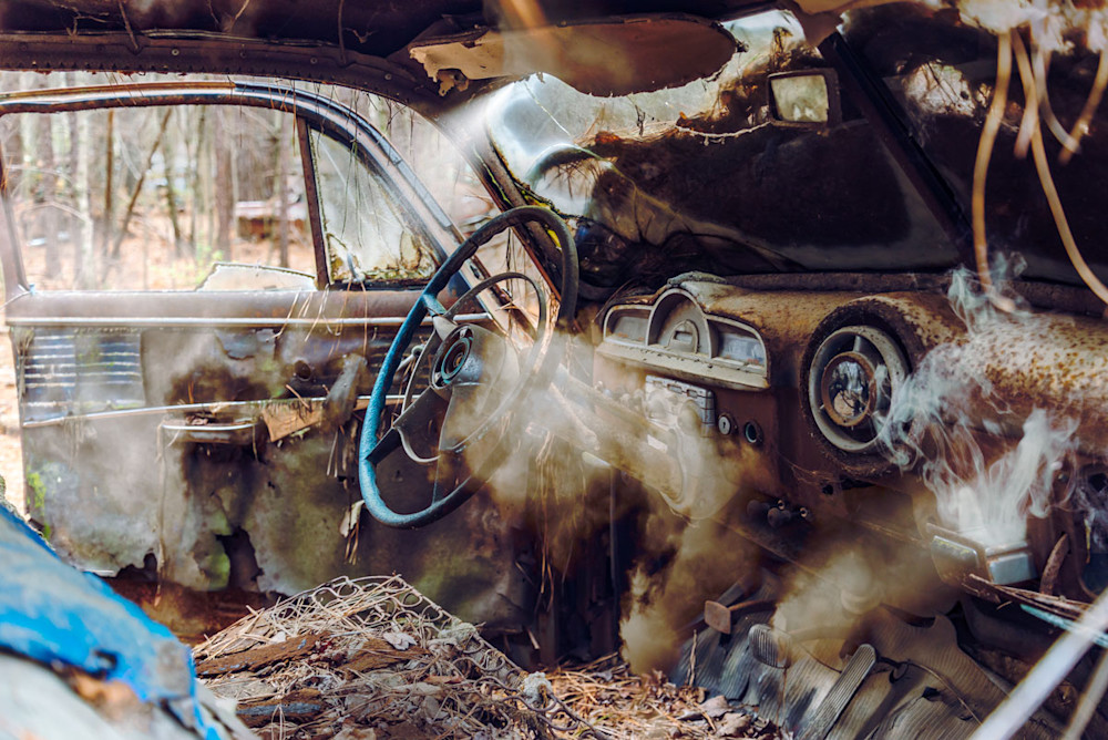 A composite fine-art photo of an old junked car with smoke rising up out of the ashtray and clouds floating through the interior