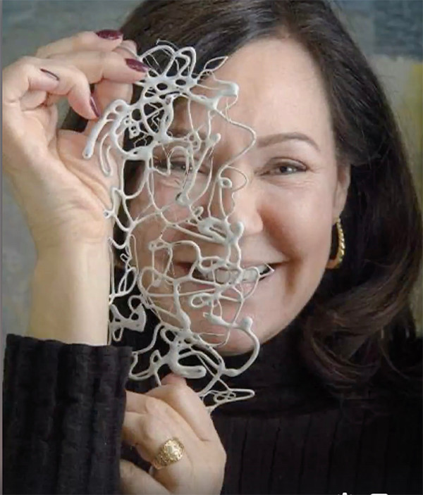 Artist Shirley Williams hold textured plastic in front of her closeup