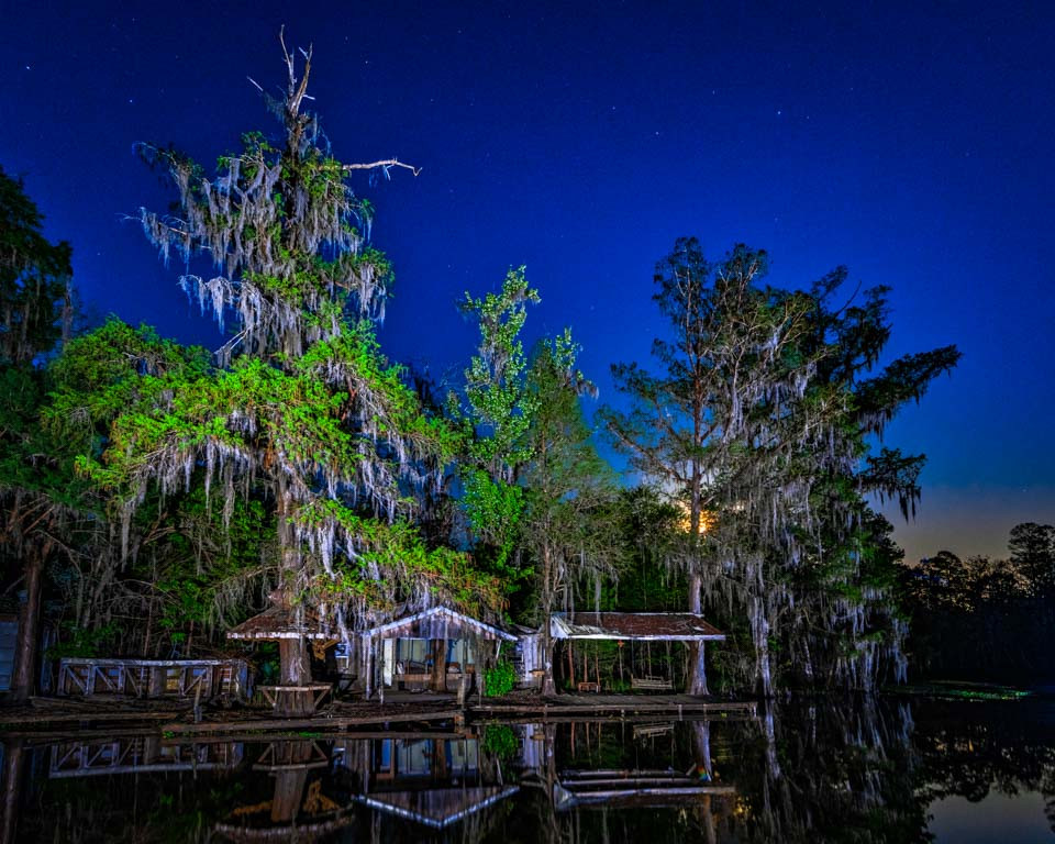 A super moon shines through the Spanish moss-draped cypress trees overlooking an abandoned camp deep in the Maurepas Swamp WMA.