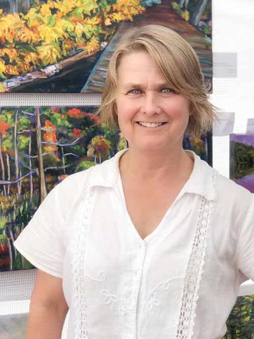 Burlington artist Janet Jardine standing in front of her paintings at an outdoor art show