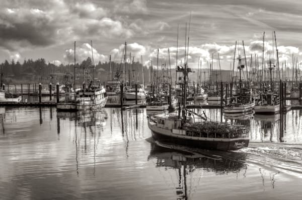 a photo of a  fishing boat heading out to sea from charleston in the coos bay area, oregon