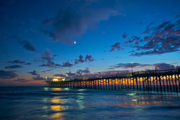 photo of the balboa pier just after sunset wity a quarter moon in the blue sky