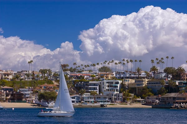 a saliboat near the end of the harbor in newprt bay with corona del mar in the background