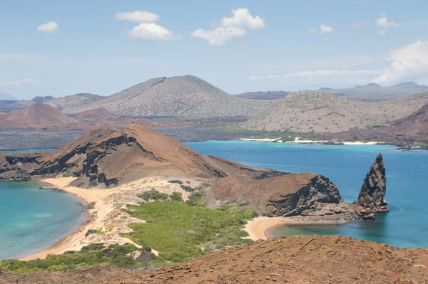 Bartolome Island, Galapagos, Ecuador; Pinnacle Rock, James Bay and Santiago Island viewed from the path leading to the summit of Bartolome Island