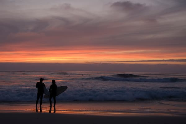Windansea, La Jolla, California; two surfers stand on the beach at  the water's edge watching the sunset