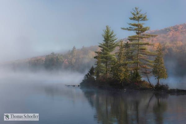 Vermont pond shrouded in fog on an autumn morning