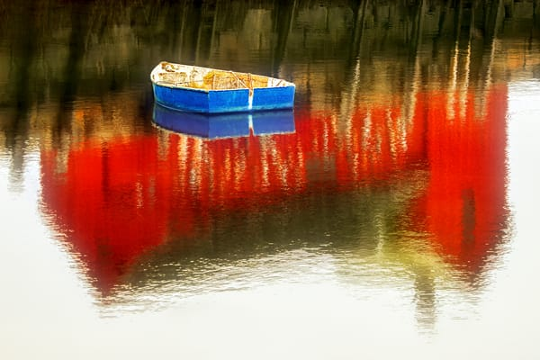 Blue Dinghy, a lone boat floating in the reflection of a red building on the shore