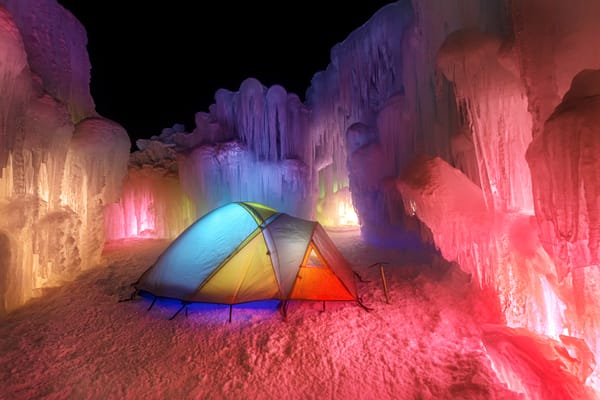 Frozen Solitude, a night scene of a colorful, lit up tent surrounded by ice
