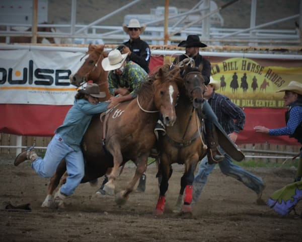 Photograph of a bull fighter loosing a bronc rider for sale as Fine Art