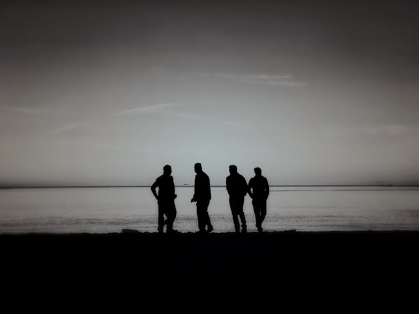 Beautiful Fine Art Paintings and Photographs by Vivian Lo – Picture of a black and white, silhouette photograph of four friends on a beach. on Originals and Prints for sale - VLo Photo
