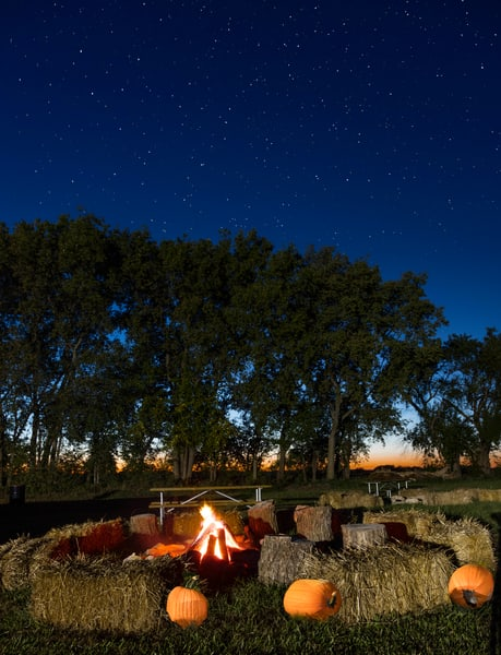 Hay Bales & Bonfires Create A Feeling of Fall In This Night photograph for sale as art.