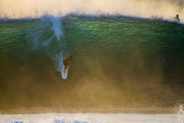 Keith Malloy charging the Bonzai Pipeline, dropping into the mist late day North Shore, Oahu