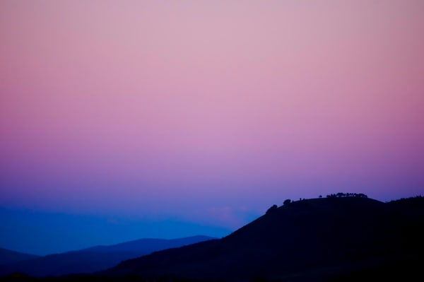 silhoutte of a mountain ridge with trees at sunrise