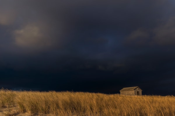 A Cape Cod beach shack under stormy skies