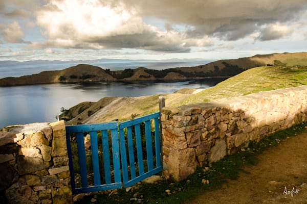 Fine art photograph of blue gate on Inca wall with fields and water behind