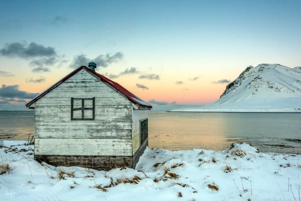 Rustic winter cabin by lake and snowy mountain in a fine art photograph print.
