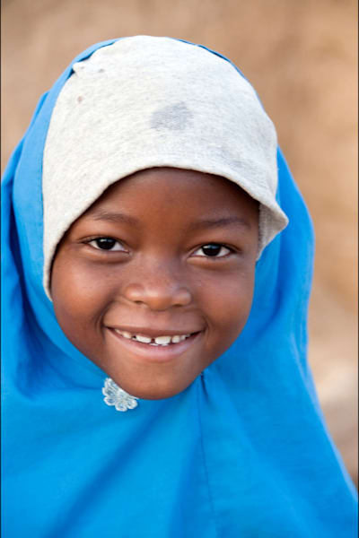 young smiling girl with blue hijab and white hoodie in fine art photograph