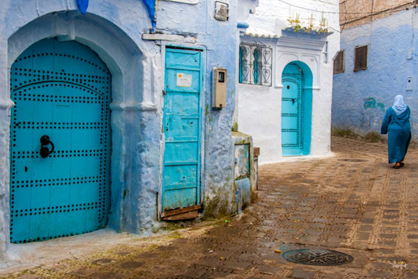 Photograph of woman in blue djellaba walking by blue doors in art rich Chefchaouen morocco