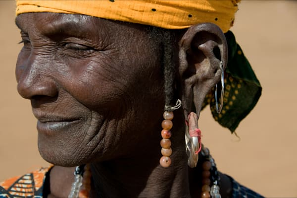 A Fulani woman with big earring and yellow head cover, in fine art photograph
