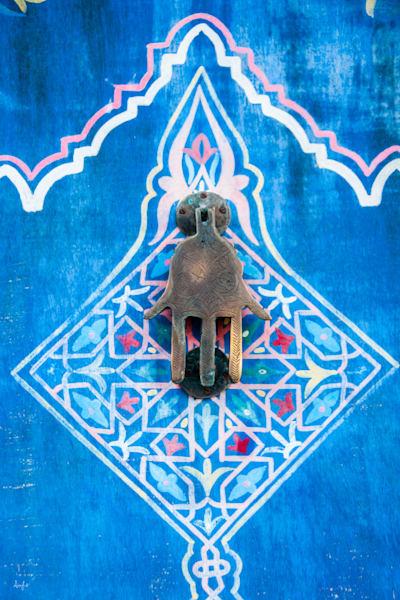 Photograph of a brass door knocker in shape of hand on colorful art door