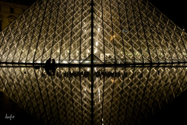 Photograph of silhouetted couple by louvre art museum at night with reflection in water