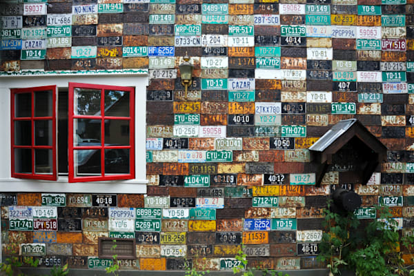 Art house covered in license plates with red window, in photograph print