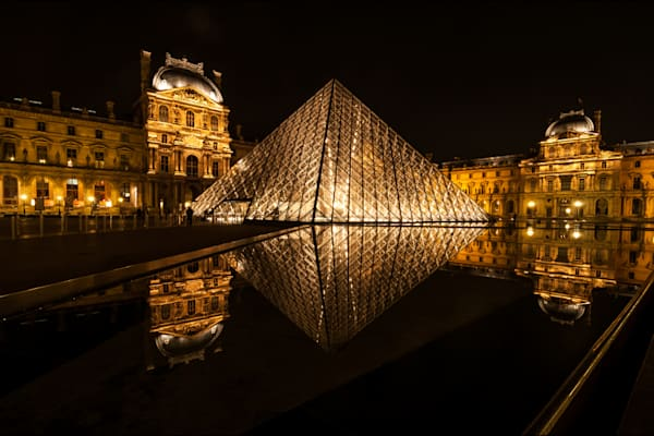photograph of the louvre art museum at night reflecting in still water.