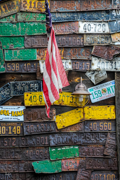 Photograph of side of art house covered in license plates and an american flag