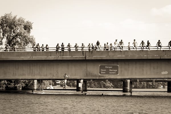 Sepia or black & white photograph of kids jumping off a dam for sale as fine art by Sage & Balm