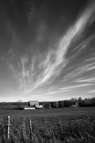 Black & white country and ruralscape photograph of dramatic clouds over a farm and barn in rural Ontario, for sale as fine art by Sage & Balm