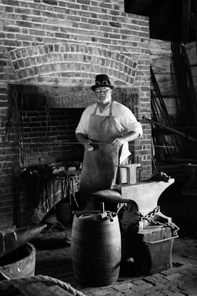 Black & white photograph of a Blacksmith at the forge at Fort George, Niagara-on-the-Lake, for sale as fine art by Sage & Balm
