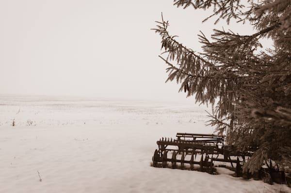 Sepia country & ruralscape photograph of an antique disc harrow plow in a foggy and snow-covered rural Ontario field, for sale as fine art by Sage & Balm